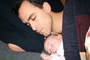 baby sleeping next to father